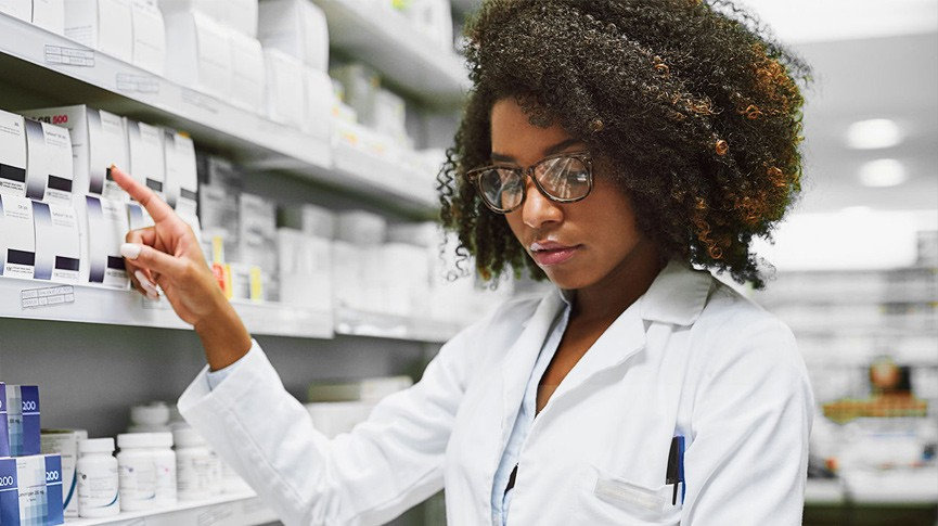 Pharmacy student pointing to pharmaceuticals on shelf